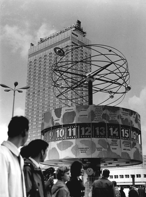 Fotografie der Weltzeituhr am Alexanderplatz aus dem Jahr 1969: Passanten bewundern das Bauwerk.